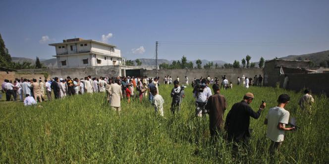 Le complexe où a été tué Ben Laden entouré de journalistes et de résidents d'Abbottabad, le 3 mai 2011.