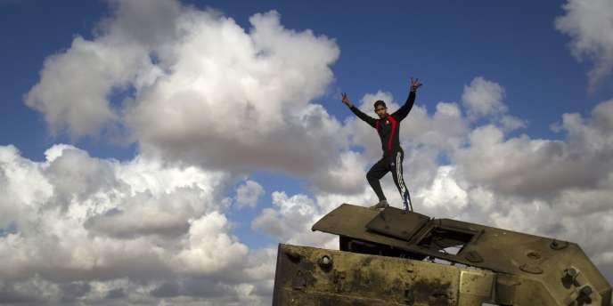 Un jeune Libyen parade sur le toit d'un véhicule des forces de Kadhafi détruit dans les faubourgs de Benghazi, dimanche 20 mars.