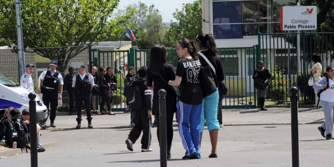 Des élèves face à des policiers en faction devant le collège Pablo-Picasso, à Garges-lès-Gonesse (Val-d'Oise), le 12 mai 2011.