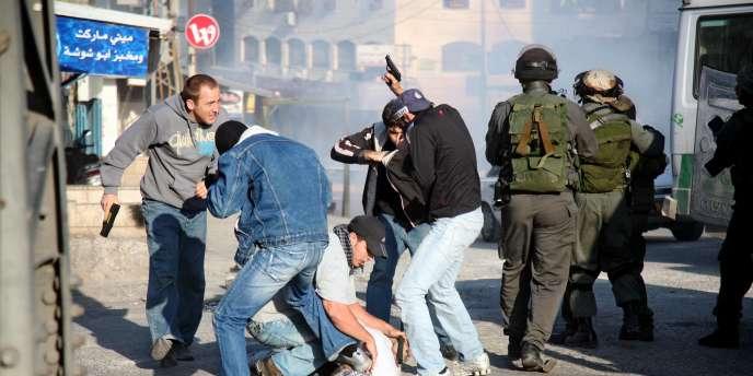 Des policiers en civil israéliens arrêtent un manifestant palestinien, vendredi 13 mai, lors des manifestations de commémoration de la
