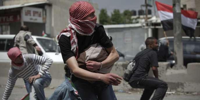 Des Palestiniens s'abritent de tirs de l'armée israélienne, le 15 mai 2011, au point de passage de Qalandiya, entre Ramallah et Jérusalem.