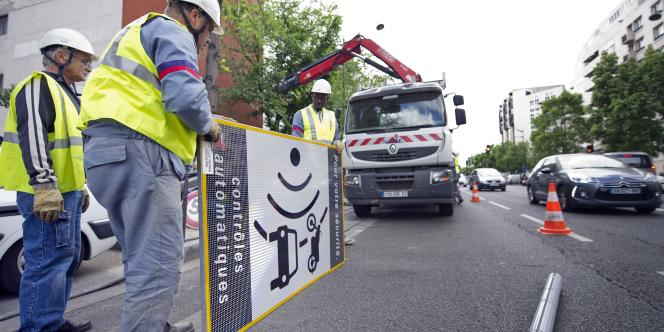 Des ouvriers démontent un panneau avertissant de la présence d'un radar fixe, le 16 mai 2011 à Paris.