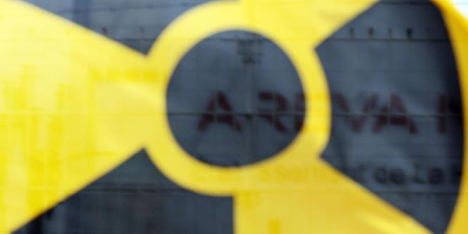 Le logo d'Areva sur son site de Beaumont-Hague vu à travers un drapeau de Greenpeace.