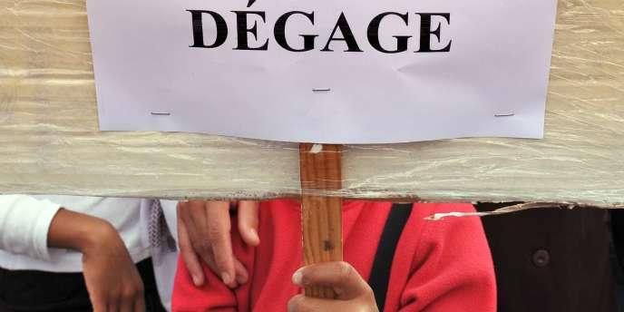 Un manifestant tient une pancarte avec le portrait du président syrien Bachar Al-Assad barré d'un