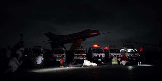 Des représentants des médias s'abritent des tirs lors de l'attaque de la base aéronavale de Mehran, le 23 mai 2011.