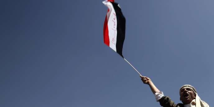 Un homme brandit un drapeau lors d'une manifestation contre le président Ali Abdallah Saleh près de l'Université de Sanaa.