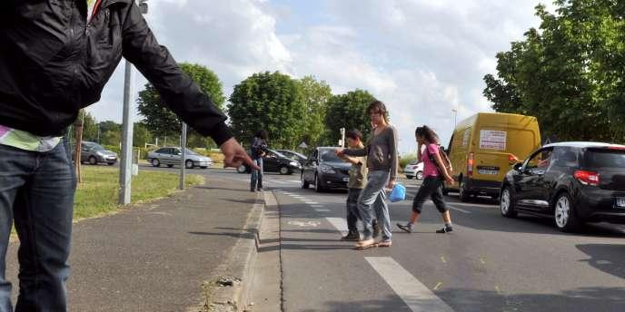 Une personne montre, le 30 mai 2011 à Joué-les-Tours (Indre-et-Loire), le lieu où une camionnette de la gendarmerie a  fauché un groupe d'une vingtaine d'enfants.