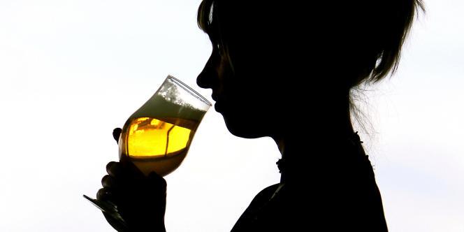Une jeune femme enceinte boit un verre de bière.