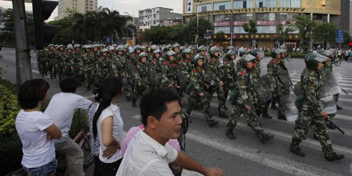 Patrouille de la police anti-émeute chinoise dans les rues de Xintang, près de Guangzhou, dans la province du Guangdong (Sud).