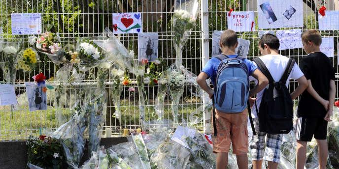 Des collégiens se recueillent devant des fleurs et messages déposés à l'entrée du collège Voltaire à Florensac, le 21 juin.