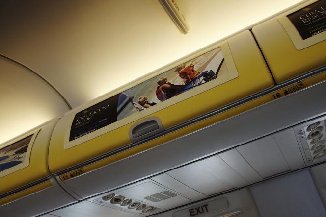 Les compartiments à bagages sont souvent décorés de messages publicitaires (marque de lunettes, hôtel en Sardaigne, office du tourisme de Malte…).