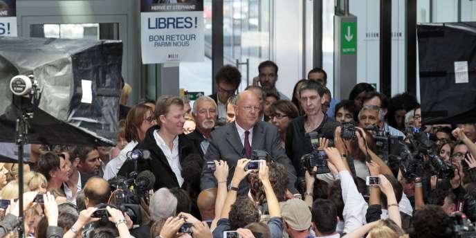 Hervé Ghesquière et Stéphane Taponier entourent Rémy Pflimlin, au siège de France Télévisions, jeudi 30 juin.