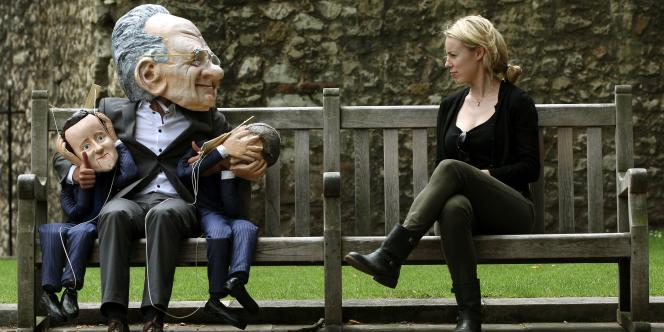 Un manifestant déguisé en Rupert Murdoch tient sur ses genoux des marionnettes de David Cameron et de son ministre de la culture, Jeremy Hunt.