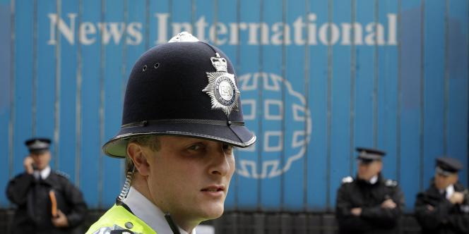 Des policiers gardent le siège de News International pendant une manifestation hostile au groupe de Murdoch, vendredi.