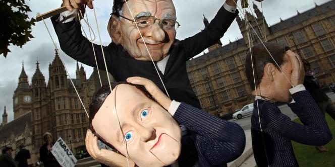 Un homme déguisé en Rupert Murdoch manipule une poupée à l'effigie de David Cameron devant le ministère de la culture britannique, vendredi 8 juillet 2011.