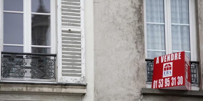 Un panneau à vendre sur un immeuble situé à Paris à proximité de la Tour Eiffel.