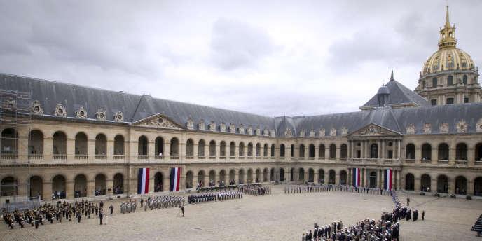 Sous une pluie persistante, le président Sarkozy est arrivé aux Invalides précédé par les familles des sept soldats qu'il a reçues à l'Elysée.