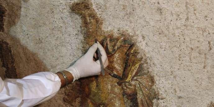 Même s'il manque une partie du fond de la mosaïque, on peut identifier la silhouette d'un homme nu représentant le dieu Apollon, qui porte un manteau sur l'épaule et une cithare.