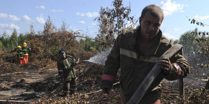Des pompiers arrosent une tourbière, à 100 kilomètres à l'est de Moscou, pour éviter une reprise d'incendie.