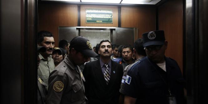 Le prévenu Carlos Antonio Carias escorté par la police à son arrivée à la Cour suprême du Guatemala, le 2 août.