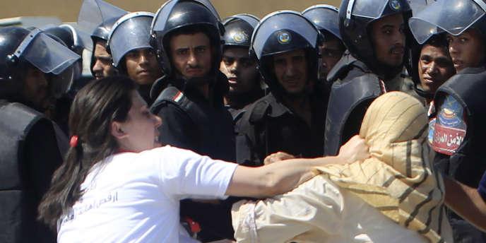 Accrochage entre deux Egyptiennes, l'une pro, l'autre anti-Moubarak, devant l'académie de police où s'est ouvert, le 3 août au Caire, le procès de l'ancien raïs.
