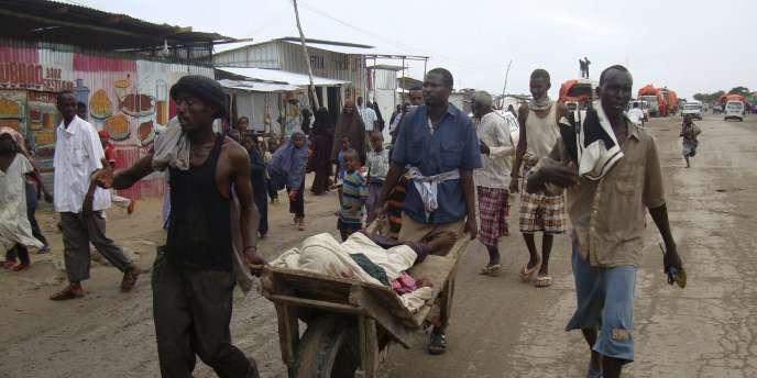 Des réfugiés somaliens transportent un homme blessé lors de combats entre deux groupes de soldats gouvernementaux, le 5 août à Mogadiscio.