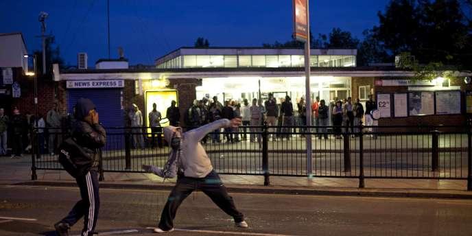 Un homme lance des briques sur des policiers, dimanche 7 août, à Enfield, dans le nord de Londres.