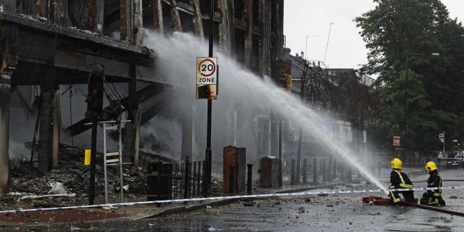 Les pompiers éteignent un immeuble incendié à Tottenham, en août 2011, suite aux émeutes qui avaient secoué ce quartier de Londres..