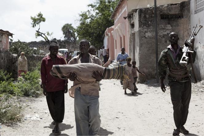 Dans le camp de Maalin, au centre de Mogadiscio, un père porte la dépouille de son enfant, victime de la rougeole.