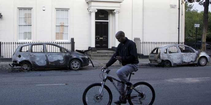 Un homme consulte son téléphone mobile alors qu'il passe devant deux voitures incendiées, le 9 août à Liverpool, où des heurts ont aussi éclaté.