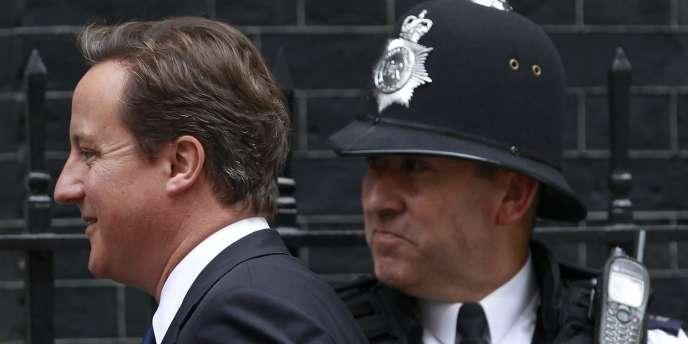 Le premier ministre britannique David Cameron marche devant un policier devant le 10 Downing Street.