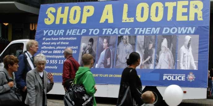 Un bus de la police affichant des photos de pillards présumés circule dans les rues de Manchester, le 12 août.