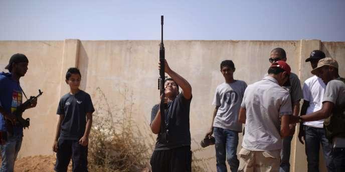 Un garçon tire en l'air lors de funérailles de combattants rebelles, vendredi 19 août, à Brega, en Libye.