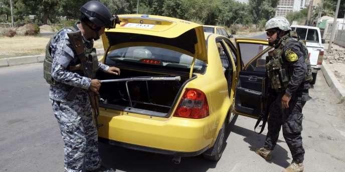 Des policiers irakiens contrôlent un véhicule, à Bagdad, le 20 août.