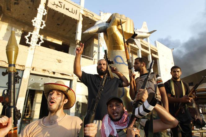 Le 23 août, des rebelles célèbrent leur victoire devant une sculpture représentant un poing écrasant un avion américain, au cœur du complexe de Bab Al-Aziziya.