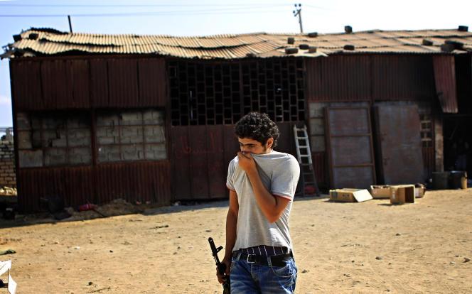 Devant le hangar qui a servi de centre de détention aux opposants à Kadhafi qui ont été retrouvés calcinés, dans le sud de Tripoli.
