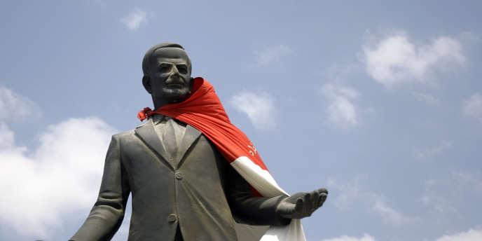 Un drapeau accroché sur la statue de l'ancien président syrien Hafez Al-Assad, à l'entrée de la ville de Homs, le 30 août 2011.