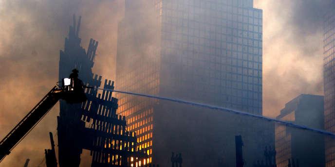 Des pompiers continuent à lutter contre le feu sur les décombres des tours jumelles, à New York, le 19 septembre 2001.