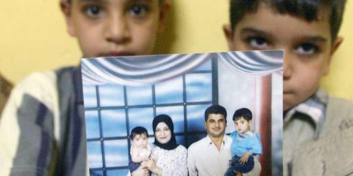 Les deux fils de Baha Mousa montrent une photographie de leur père, un civil irakien mort alors qu'il était détenu par l'armée britannique en 2003
