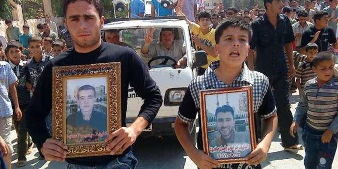 Sur cette capture d'écran de la télévision d'opposition Shaam News, des manifestants portent le portrait des victimes de la répression dans la province d'Idlib, le 9 septembre 2011.
