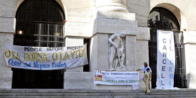Des pancartes s'affichent devant la Bourse de Milan, lundi 5 septembre, pour protester contre le plan de rigueur soumis au vote du Parlement italien.