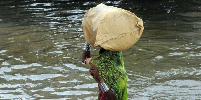 Une habitante du village de Golarchi, dans le district de Badin au Pakistan, traverse une rue inondée, le 13 septembre.