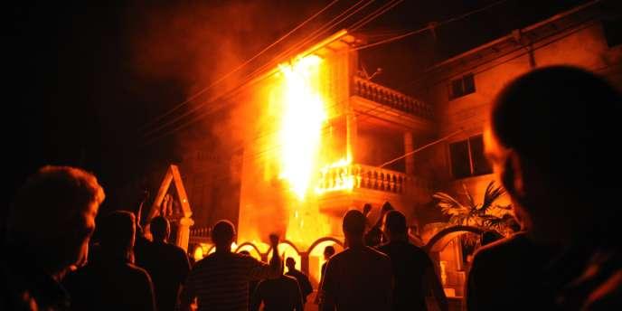 Une foule observe l'incendie d'une maison du chef de clan rom Kiril Rashkov, dans le village de Katunitsa, en Roumanie, le 24 septembre.