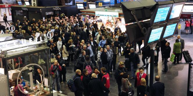 Des usagers devant des écrans d'information, le 6 octobre 2011 à la gare de l'Est, à Paris.
