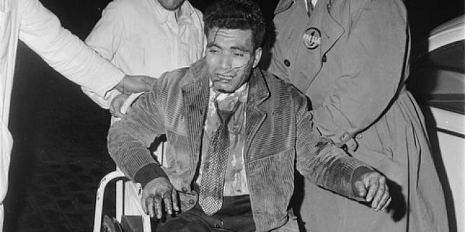 Un Algérien blessé est emmené par le photographe Elie Kagan et un journaliste américain à l'hôpital de Nanterre, le 17 octobre 1961.