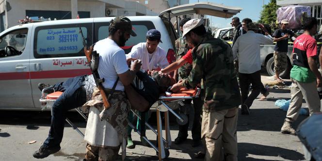 Un combattant rebelle porté dans une ambulance à Syrte, le 14 octobre.