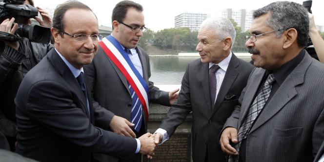 François Hollande, accompagné du maire d'Asnières, Sébastien Pietrasenta, rend hommage aux Algériens jetés dans la Seine en 1961, sur le pont de Clichy-la-Garenne, le 17 octobre 2011.