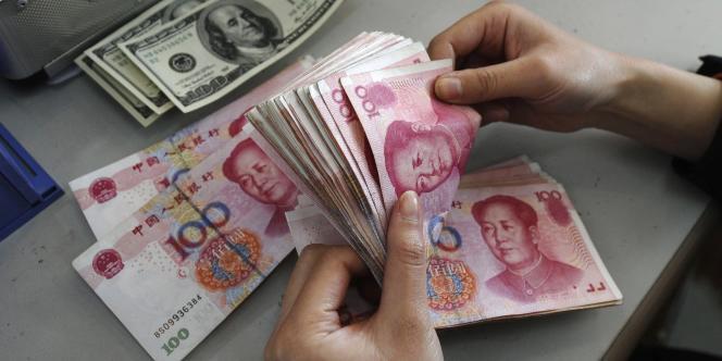 Des yuans et des dollars dans une banque chinoise en mars 2010.