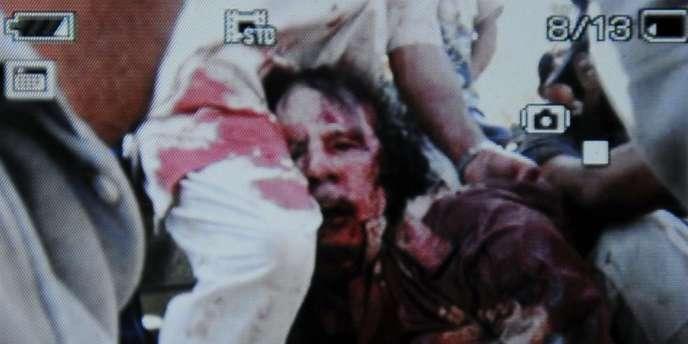 Capture d'écran réalisée à Syrte par un photographe de l'AFP sur un appareil montrant la vidéo d'un homme qui serait Mouammar Kadhafi, capturé près de Syrte après une attaque de l'OTAN.