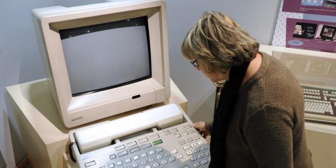 Une femme regarde une maquette géante de Minitel au musée des télécommunications de Rennes.